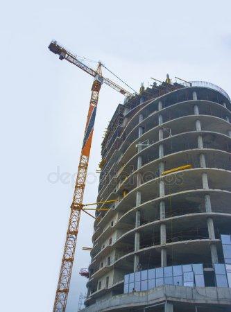 Кран и современное остекление здания — стоковое фото