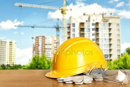 Строительные инструменты и шлем на деревянный стол и строительство строительство фона — стоковое фото