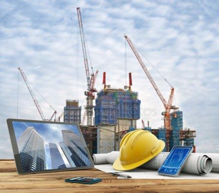 Чертежи и защитный шлем над столом в строительной площадки — стоковое фото